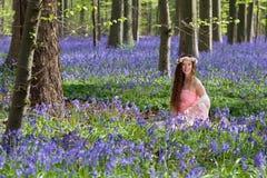 愉快的妇女在会开蓝色钟形花的草森林里 免版税库存图片