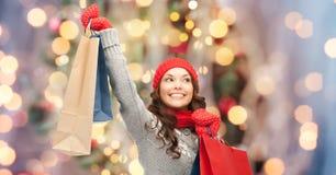 愉快的妇女在冬天穿衣与购物袋 免版税库存照片