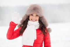 愉快的妇女在冬天裘皮帽挥动的手上户外 免版税库存照片