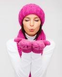 愉快的妇女在冬天给吹在棕榈穿衣 库存图片