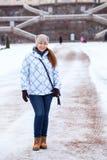 愉快的妇女在冬天给在宫殿楼梯前面的身分穿衣 免版税库存照片