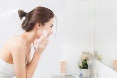 愉快的妇女在卫生间里洗涤与泡沫的皮肤 免版税库存照片