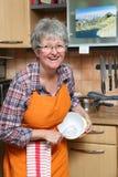 愉快的妇女在厨房里 免版税图库摄影