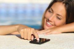 愉快的妇女在发短信在一个巧妙的电话的假期沐浴在游泳池 图库摄影