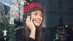 愉快的妇女在坐在一个舒适咖啡馆的电话谈话在冷的冬日 股票录像