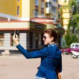 愉快的妇女在城市拍一张selfie照片 免版税库存图片