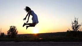 愉快的妇女在天空中跳,接触她的脚跟,在尼斯日落在Slo Mo 股票视频