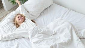 愉快的妇女在她的床上醒早晨 股票录像