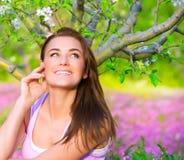 愉快的妇女在开花的庭院里 免版税库存照片