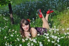 愉快的妇女在春天庭院是在颜色,与红色鞋子 图库摄影