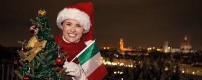 愉快的妇女在有圣诞树和意大利旗子的佛罗伦萨 免版税库存图片