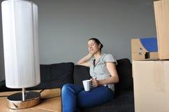 愉快的妇女在沙发放松在移动期间入一个新的家 库存照片