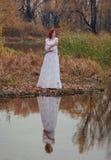 年轻愉快的妇女在河附近的一个公园秋天季节的 免版税图库摄影