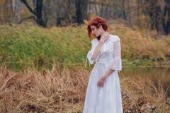 年轻愉快的妇女在河附近的一个公园秋天季节的 库存图片