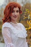 年轻愉快的妇女在河附近的一个公园秋天季节的 免版税库存图片