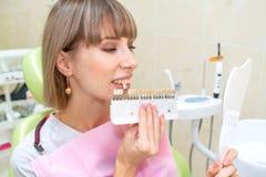 愉快的妇女在牙科方面拾起牙瓷漆的颜色 免版税图库摄影
