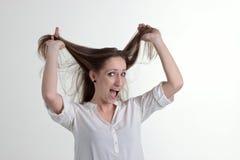 愉快的妇女在白色背景拿着她头发被隔绝 免版税库存照片