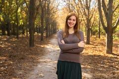 愉快的妇女在秋天公园 免版税库存图片