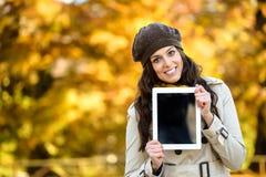 愉快的妇女在秋天的拿着数字式片剂 免版税库存照片