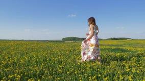 愉快的妇女在风振翼的礼服的一个开花的黄色领域走 影视素材