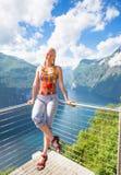 愉快的妇女在Geiranger海湾放松 女孩在挪威享受好天气 免版税库存照片