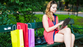 年轻愉快的妇女坐与五颜六色的购物袋和片剂的一条长凳。 库存照片
