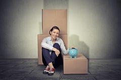愉快的妇女坐与许多箱子的地板,搬出 库存照片