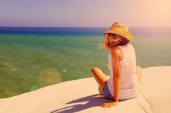 愉快的妇女坐海边 免版税库存图片