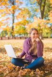 愉快的妇女坐象草的地面使用膝上型计算机 库存照片
