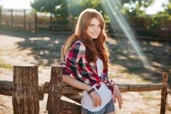 愉快的妇女女牛仔身分和放松在大农场 库存照片