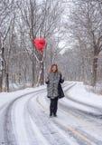 愉快的妇女常设外部在拿着r的一多雪的2月天 库存照片