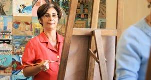 愉快的妇女微笑的绘画画象在艺术学校 免版税库存照片