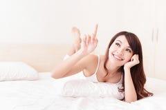 愉快的妇女微笑,当说谎在床上时 库存照片
