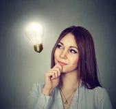 愉快的妇女想法的看明亮的电灯泡 免版税库存照片