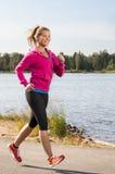 愉快的妇女慢跑者培训在公园 免版税库存照片