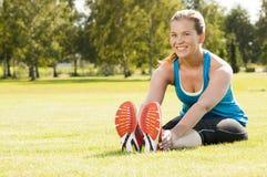 愉快的妇女慢跑者培训在公园 免版税库存图片