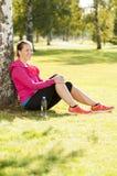 愉快的妇女慢跑者培训在公园 库存图片