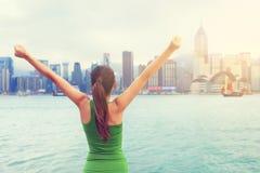 愉快的妇女成功在日落的香港市 免版税图库摄影
