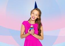 愉快的妇女或青少年的女孩用生日杯形蛋糕 免版税库存图片