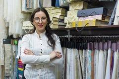 愉快的妇女所有者画象与横渡的胳膊在内部织品商店,背景织品样品的 小企业家纺织品 免版税库存图片
