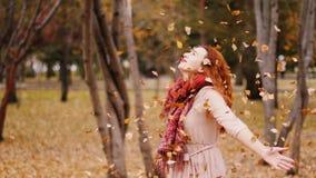 愉快的妇女投掷的叶子在秋天 快乐和激动的少妇获得乐趣在秋天公园 库存图片