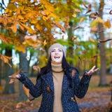 愉快的妇女投掷的叶子画象在公园 库存图片