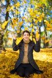 愉快的妇女投掷的秋叶在公园 免版税库存照片