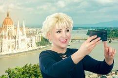 愉快的妇女拍在旅行旅行的selfie照片 免版税库存图片