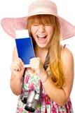 愉快的妇女持与票的一本护照 免版税库存图片