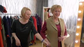 愉快的妇女时尚尝试陈列室美发师帮助 股票视频