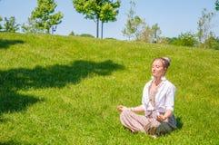愉快的妇女是在莲花姿势的思考的开会在草草坪 免版税库存图片