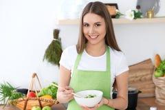 年轻愉快的妇女是烹调或吃新鲜的沙拉在厨房里 食物和健康概念 免版税库存图片
