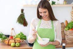 年轻愉快的妇女是烹调或吃新鲜的沙拉在厨房里 食物和健康概念 免版税库存照片