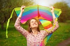 愉快的妇女是猛冲每在春天草甸的风筝 库存照片